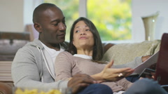 4K Relaxed couple at home, doing household accounts on the sofa - stock footage