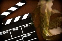 Movie clapper board detail and unrolled  filmstrip - stock photo