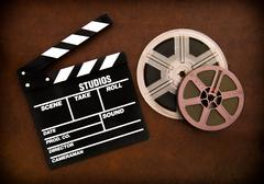 Movie clapper board and film reels detail on wooden floor - stock photo