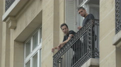 Men standing on the balcony and smoking, Paris Stock Footage