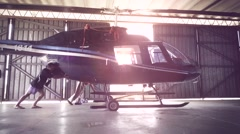 Men pushing chopper inside hangar Stock Footage