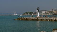 Kusadasi, Turkey -  Fisherman on the Kusadasi Promenade and Statue of Peace. Stock Footage