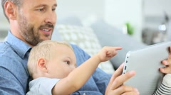 Daddy and baby boy playing with digital tablet - stock footage
