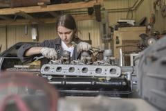 Mechanic repairing car engine at garage Kuvituskuvat