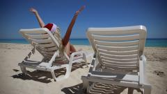Woman in Santa Claus Hat sitting on sunbed near  tropical calm beach Stock Footage