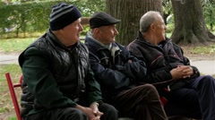 Elderly sitting on a bench in the park and socialize, pensioners, relaxation. Stock Footage