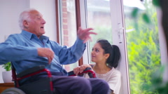 4K Caring young home support worker with elderly gentleman in his home - stock footage