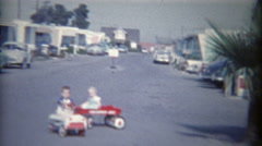 1962: Kids in kiddie car and wagons pulled around trailer home park. - stock footage