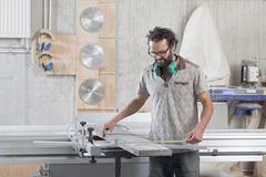 Stock Photo of Male carpenter measuring lumber in workshop