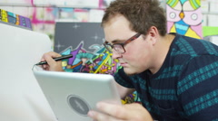 4K Modern graphic artist in his studio, drawing & looking at a computer tablet. - stock footage