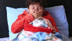 Child lying in bed and sneezing Stock Footage