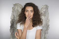 Portrait of beautiful woman in angel wings against gray background Kuvituskuvat
