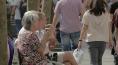 Elderly people sitting on a bench and drinking coffee on Champs-Elysees, Paris Stock Footage