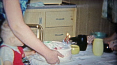 Stock Video Footage of 1962: Aunt smokes cigarette while kid blows out 2nd birthday cake candle.