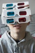 A boy wearing a large amount of 3-D glasses Stock Photos