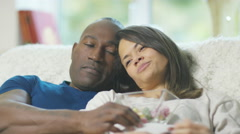 4K Pregnant couple relaxing at home, woman rests bowl of snacks on her bump - stock footage