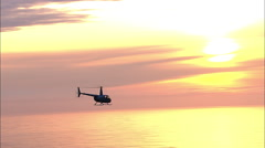 Helicopter Flying Over Ocean Sunset Aerial - stock footage