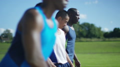 4K Athletes in training at the running track, stretching out before a race Stock Footage