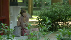 Woman talking on phone near a pagoda pavilion, Warsaw Stock Footage