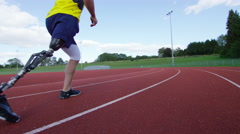 4K Disabled athlete with prosthetic leg running at the running track Stock Footage