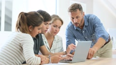 Teacher with group of students working on laptop computer - stock footage