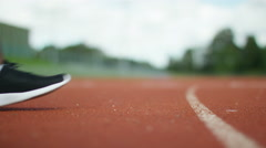 4K Close up on hands & feet of unrecognisable athlete at the running track  - stock footage