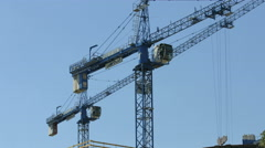 View of two tower cranes on a blue sky backgroung in Warsaw Stock Footage