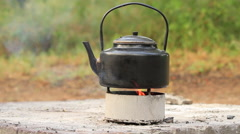 Kettle boiling on a Camp Fire WS Stock Footage