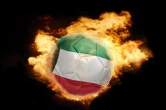 football ball with the flag of kuwait on fire - stock photo