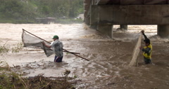 Fishermen Tackle Raging Flood Waters In River Stock Footage