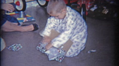1958: Kid opens Christmas gift of army men in a box. - stock footage
