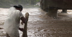 Fishermen with net Tackle Raging Flood Waters In River Stock Footage
