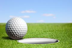 Golf ball at the hole - stock illustration