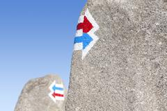 Trail signs painted on rock, choice or dilemma concept. - stock photo