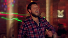 A man  with a beard, dancing and smiling in a nightclub Stock Footage