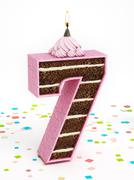 Number 7 shaped chocolate birthday cake with lit candle - stock illustration