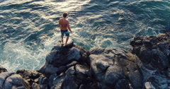 Aerial Flight Over Young Man Jumping Off Ocean Sea Cliff into Sunset. Stock Footage