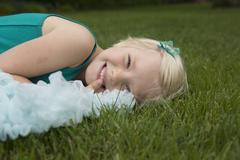 Portrait of smiling girl lying on grassy field at backyard Stock Photos