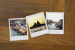 Instant print photographs of famous places on wooden table Stock Photos