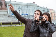Couple making photo on camera outdoors - stock photo