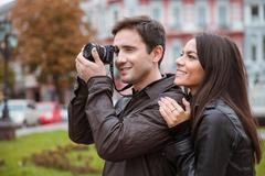 Couple traveling and making photo on camera - stock photo