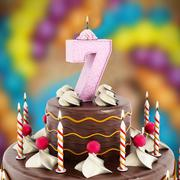 Birthday cake with number 7 lit candle - stock illustration