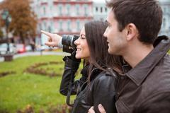 Couple making photo on camera outdoors Stock Photos