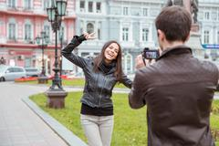 Man making photo of laughing woman outdoors Stock Photos