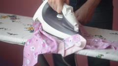 Young woman ironing baby clothes on an ironing board at home Stock Footage