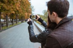 Couple making photo on smartphone of autumn park Stock Photos