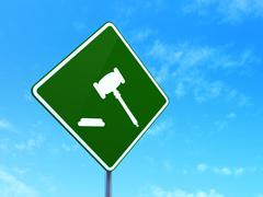 Law concept: Gavel on road sign background - stock illustration