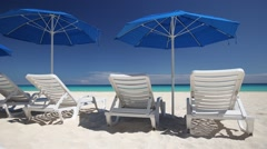 Caribbean beach with blue sun umbrellas and white  sunbeds Stock Footage