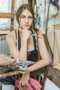 Portrait of beautiful female painter sitting on chair in studio Stock Photos