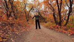 Blonde girl does excercises in the autumn forest - stock footage